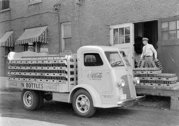 Delivery man loading bottle cases of Coca-Cola soda onto the open bed of an International C-300 delivery truck, 1936