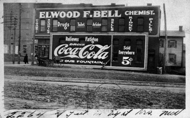 Elwood F. Bell, Chemist, office covered with Coca-Cola and other ads 1911